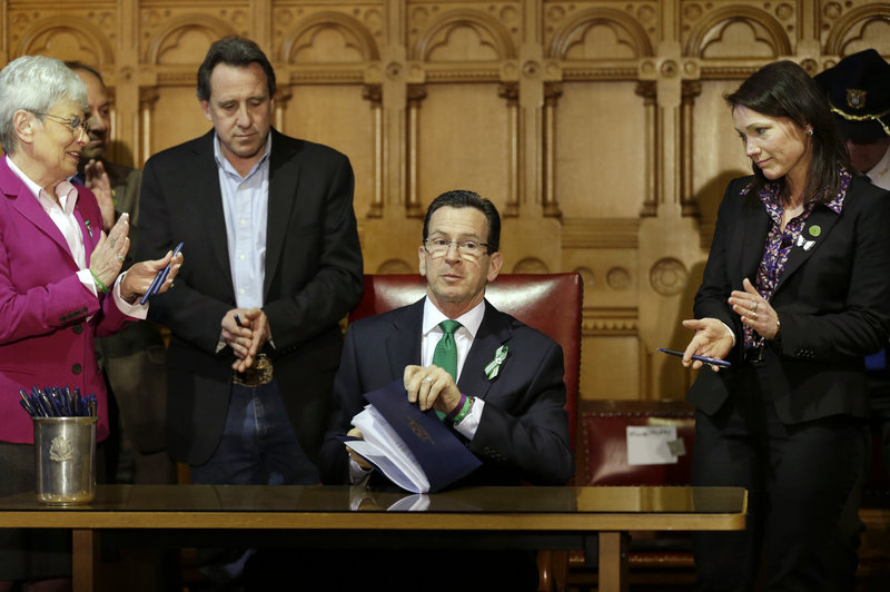 Connecticut Gov. Dannel P. Malloy, center, finishes signing legislation that includes new restrictions on weapons and large-capacity ammunition magazines, at the Capitol in Hartford, Conn., on Thursday. Malloy is applauded by Neil Heslin, father of Sandy Hook shooting victim Jesse Lewis, third from left, Nicole Hockley, right, mother of Sandy Hook School shooting victim Dylan, and Conn. Lt. Gov. Nancy Wyman.