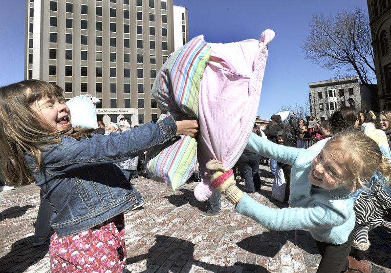 Evie King and Jocelyn Ruffner, both 8 and from Yarmouth, laugh while swinging away with pillows at an International Pillow Fight Day event in Monument Square in Portland on Saturday.