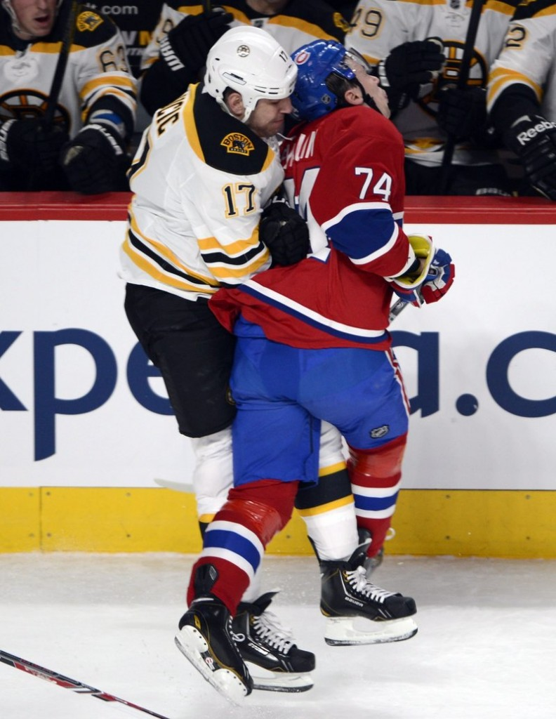 Milan Lucic of the Bruins checks Canadiens defenseman Alexei Emelin from behind Saturday night during Montreal's 2-1 victory at home.