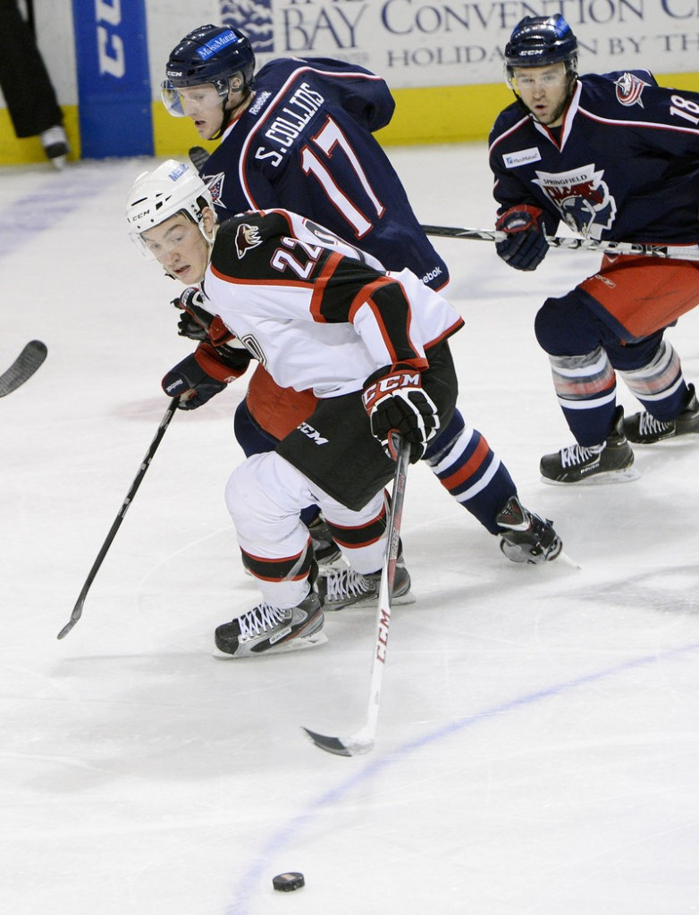 Pirates forward Phil Lane reaches for the puck as Sean Collins and Matthew Ford of the Springfield Falcons look on Sunday at the Cumberland County Civic Center. The Pirates lost, 4-2.