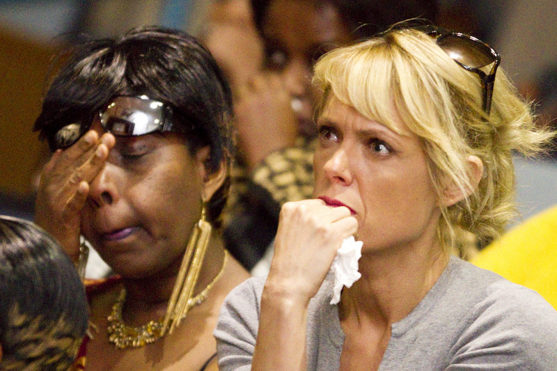 Claudette Muteteli, left, a native Rwandan, and friend Kellisha Decarlo react while watching a documentary about genocide in Rwanda during the 19th Commemoration of Genocide against the Tutsi on Sunday. Muteteli is the only one of her nine immediate family members who escaped the genocide of 1994 that killed more than 800,000 Tutsis.