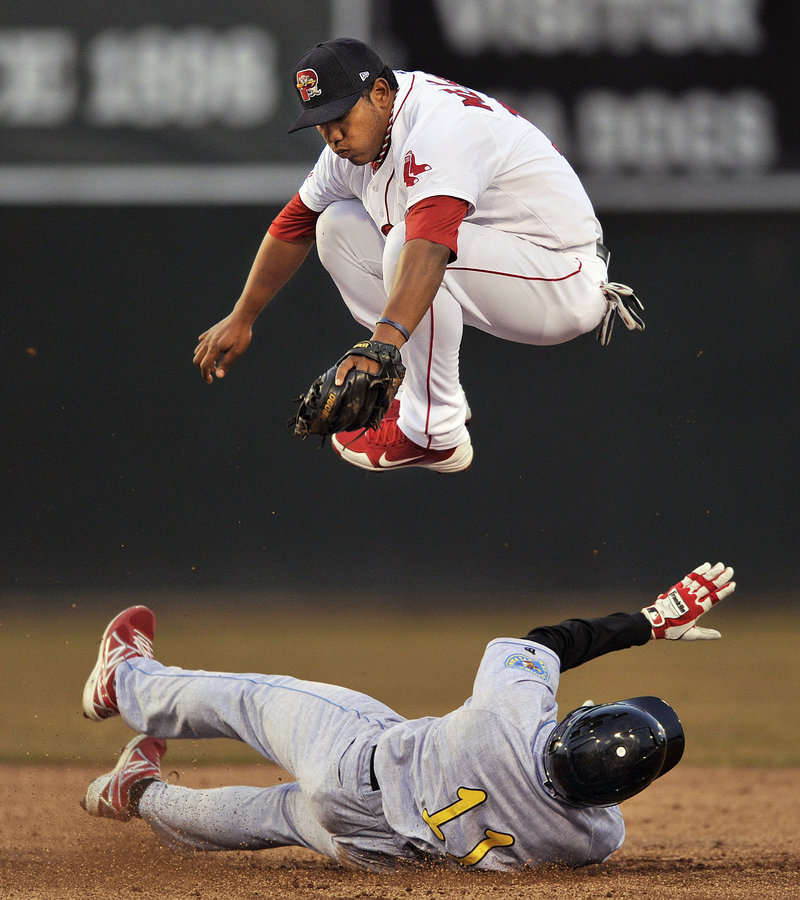 Heiker Meneses of the Sea Dogs leaps over Reading's Derrick Mitchell, who broke up a double play in the fifth inning Tuesday night at Hadlock Field.