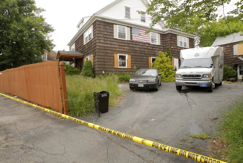 In this July 2009 file photo, police search then-alleged killer Rory Holland's house at 58 South St. in Biddeford. The home, which fell into disrepair, has been demolished and will become a park.