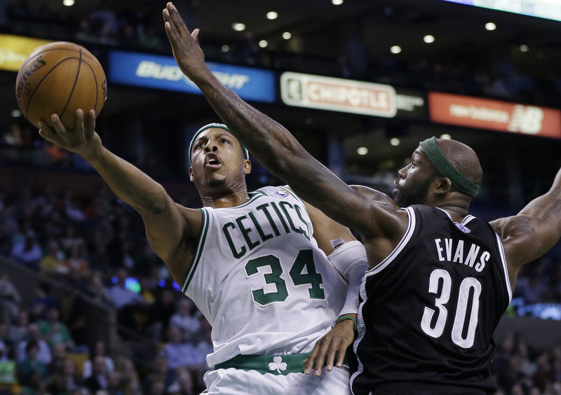 Paul Pierce, who scored a team-high 23 points Wednesday night for the Boston Celtics, drives past Reggie Evans of the Brooklyn Nets for a layup during the Nets' 101-93 victory at Boston.