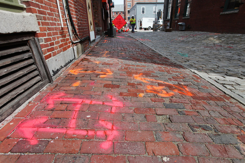 Spray paint marks where utility lines are located under Wharf Street and its sidewalks as Unitil replaces cast-iron natural gas lines in the Old Port with new plastic lines.
