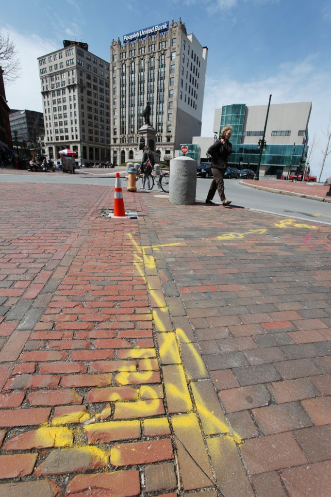 Yellow spray paint marks the underground locations of natural gas lines near Monument Square in Portland. The markings are required before digging projects so contractors can avoid rupturing lines.