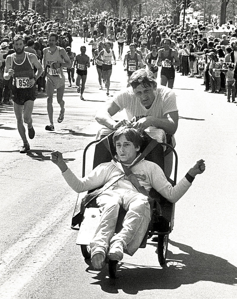 In this circa 1980s photo, Dick Hoyt, rear, pushes his son Rick as they compete in the Boston Marathon, passing along Heartbreak Hill in Newton, Mass.