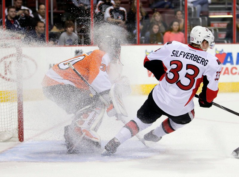 Philadelphia goaltender Ilya Bryzgalov gets a snow shower from Ottawa forward Jakob Silfverberg during first-period action of Thursday's game in Philadelphia won by the Senators, 3-1.