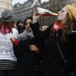 """Anti-Thatcher protesters react to the death of the former British prime minister in London on Monday. """"The Witch is Dead"""" on the T-shirt refers to an anti-Thatcher song."""