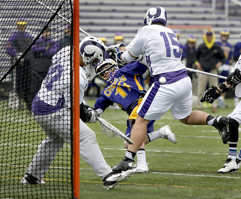 James Doyle of Deering knocks down Hilmar Smith of Cheverus as Deering goalie Riley Archer concentrates on the ball Friday during Cheverus'12-6 victory in a season-opening SMAA boys' lacrosse game at Deering High. Cheverus is the defending Eastern Class A champion.