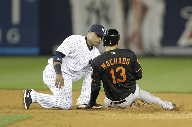Yankees second baseman Robinson Cano tags out Manny Machado of the Orioles to complete a triple play in the eighth inning of New York's 5-2 win Friday night at Yankee Stadium.