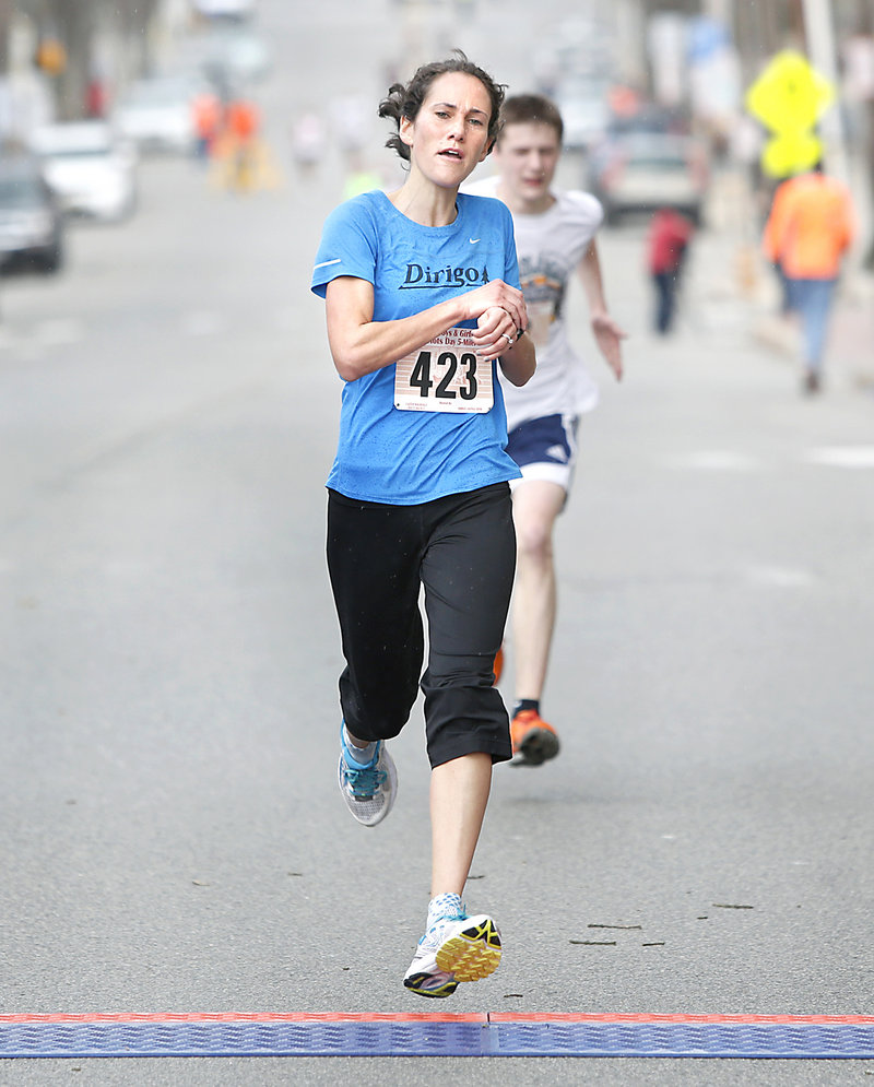 Women's winner Meredith Anderson of Portland crosses the finish line during the 84th Boys and Girls Club Patriots Day 5-mile road race in Portland on Sunday. Ellsworth native Louie Luchini was the men's winner.