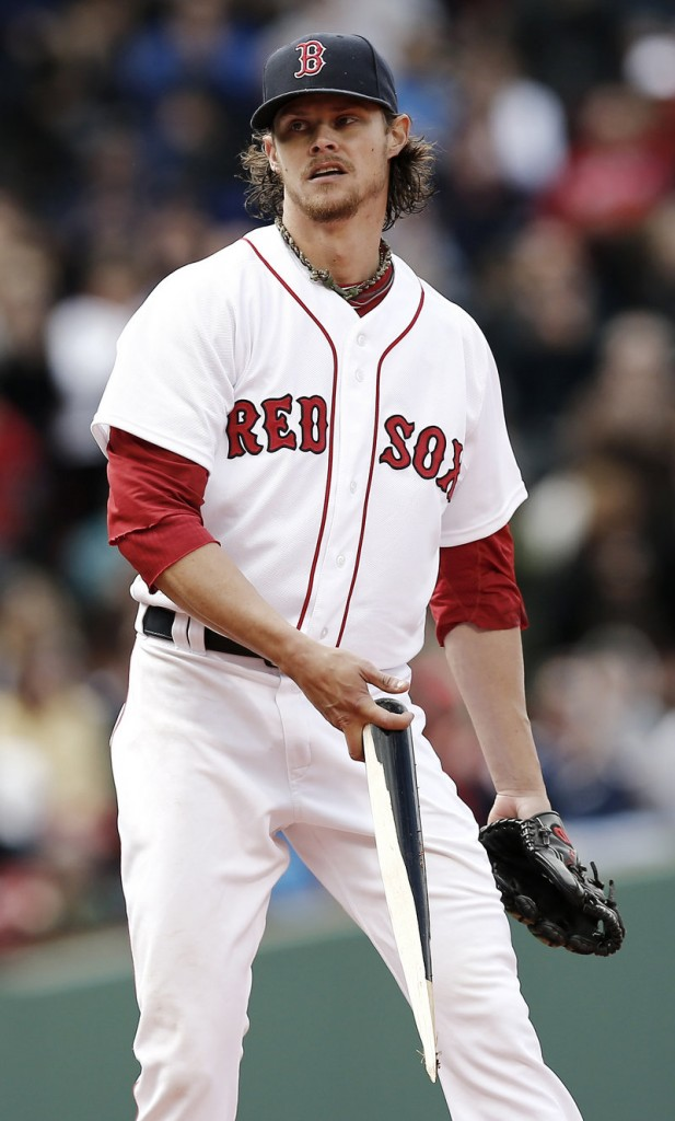 Clay Buchholz picks up the broken bat of Tampa Bay's Kelly Johnson after Johnson looped a liner into short right field in the eighth inning for the Rays' first hit of the game.