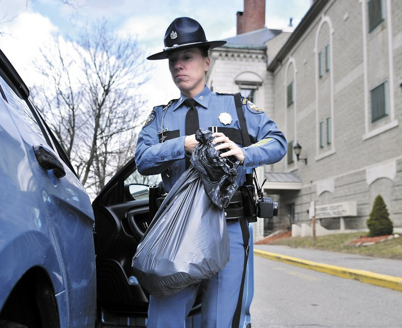 Maine State Police Trooper Diane Perkins-Vance carries a bag of Christopher Knight's clothing Sunday at the Kennebec County jail, where she filed new charges against him.