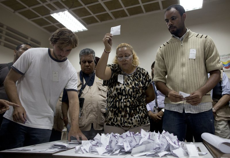 Polling workers count votes Sunday in Caracas. Millions of Venezuelans were lifted out of poverty under Hugo Chavez, but many also believe his government plundered much of the $1 trillion in oil revenues during his tenure.