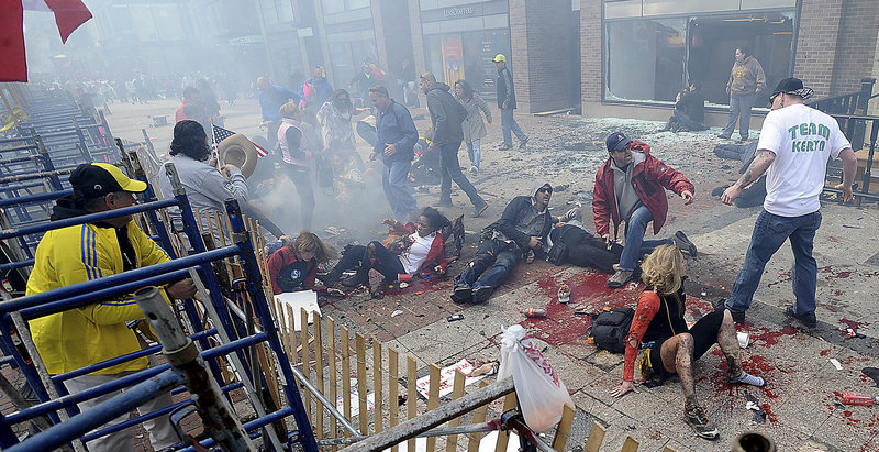 Injured people and debris lie on the sidewalk near the Boston Marathon finish line following an explosion in Boston, Monday, April 15, 2013. (AP Photo/MetroWest Daily News, Ken McGagh)
