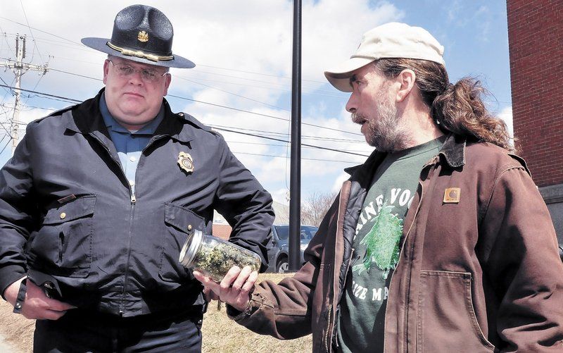 "Marijuana advocate Donald Christen shows a jar of the weed to Skowhegan Deputy Police Chief Dan Summers during the Patriots Day ""smoke-in"" on the steps of the Somerset County Courthouse. The event is staged annually to support full legalization of the drug."