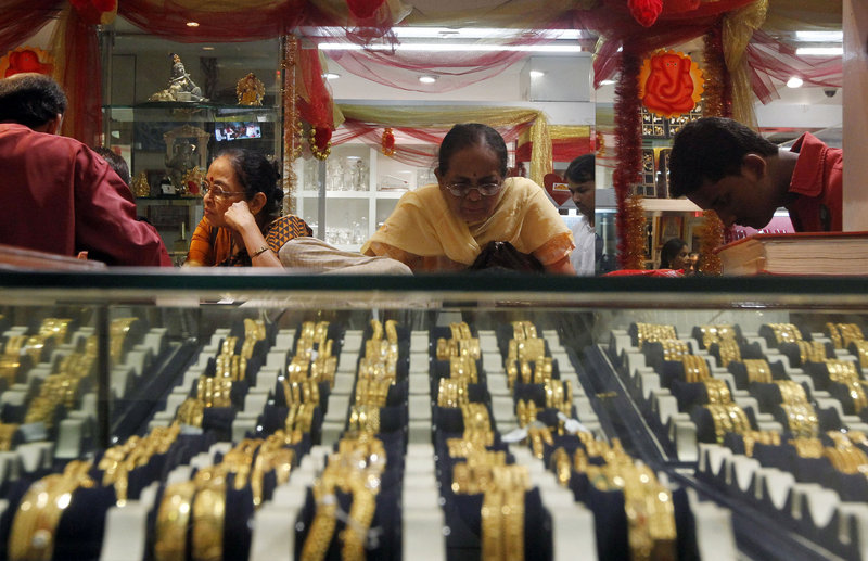 An Indian woman looks at a display of gold jewelry at a shop in Mumbai, India. The price of gold dropped 13 percent in two days recently.