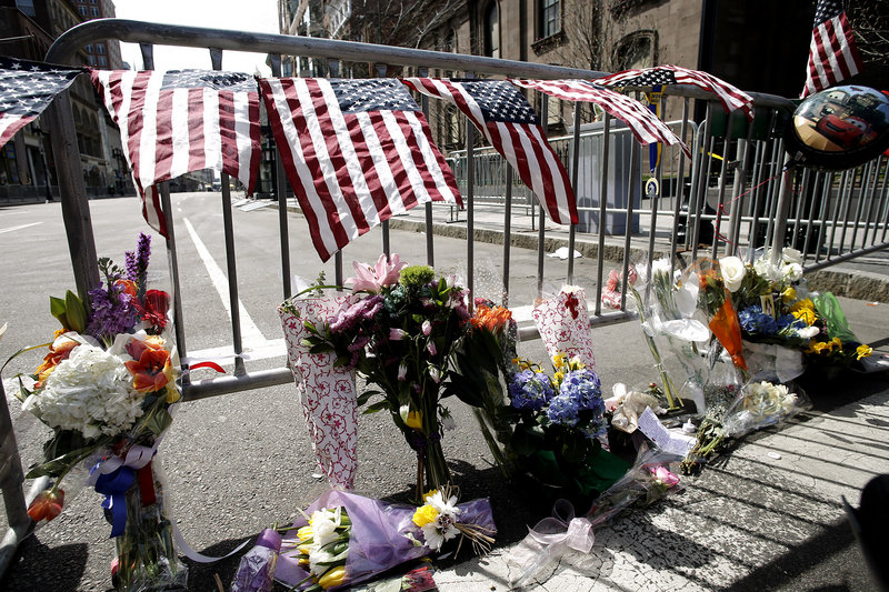 Flowers sit at a police barrier near the finish line of the Boston Marathon on Tuesday.