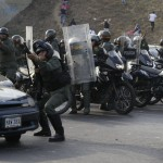 Riot police fire rubber bullets at demonstrators throwing rocks after opposition supporters blocked a highway Monday in Caracas, Venezuela, to protest election results.