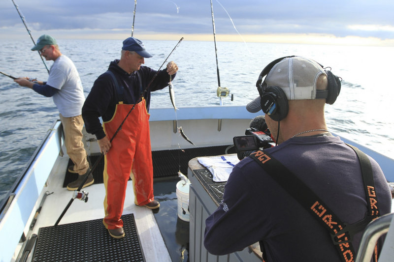 "Cameraman River Hagg films first mate Bruce Hebert of North Waterboro, second from left, as he rigs bait fish with deckhand Kevin Twombly, left, aboard the fishing boat Lisa & Jake in Gloucester, Mass., on the current season of ""Wicked Tuna,"" airing on the National Geographic Channel."