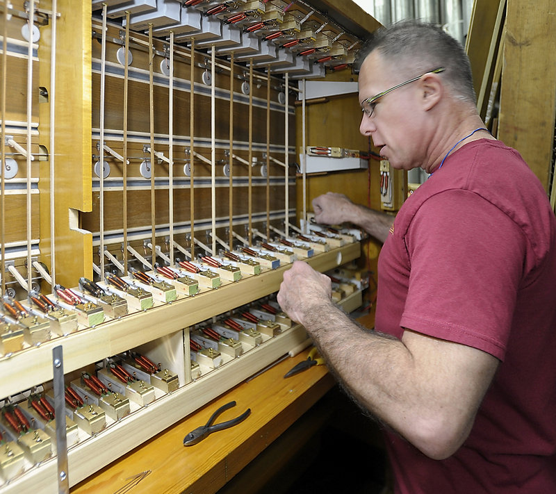Organ technician David DeBlois applies his expertise to making adjustments on the organ's internal parts.