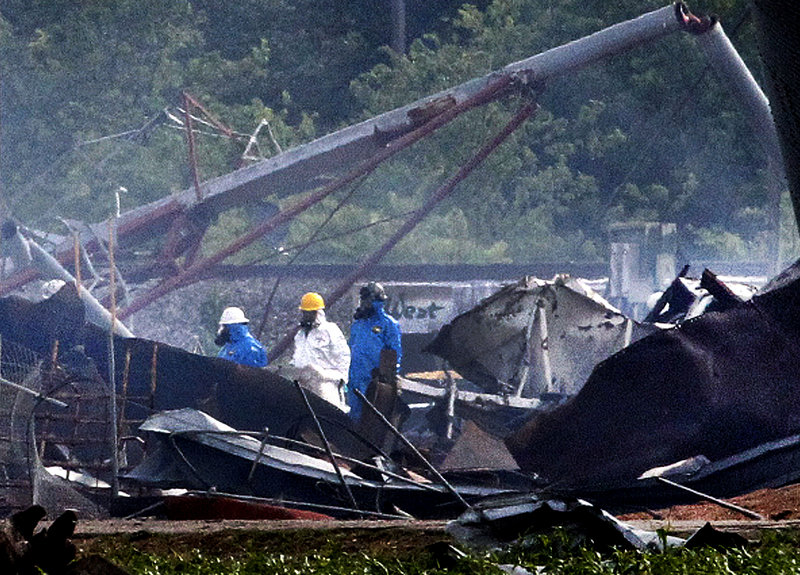 Searchers in protective suits walk through the blast zone Thursday of the fertilizer plant that exploded Wednesday night in West, Texas.