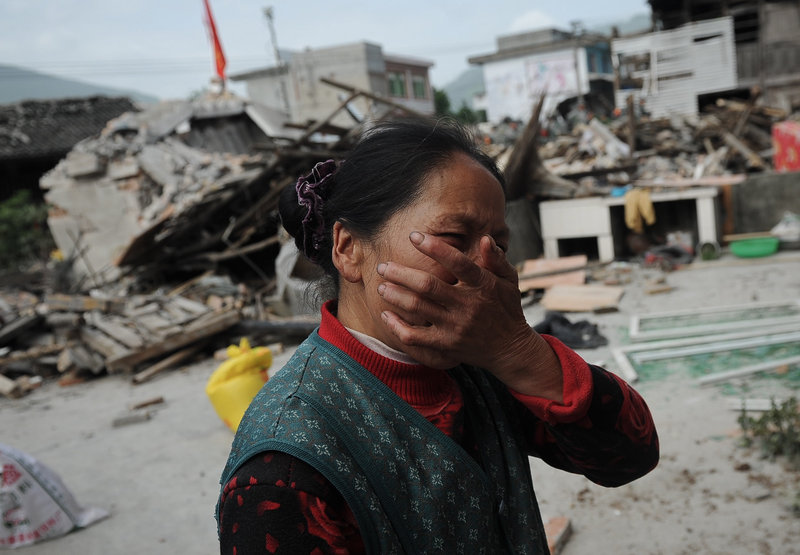 A village woman reacts after her house was damaged by the earthquake in Ya'an, also in Lushan county. The quake triggered landslides and disrupted phone and power connections in the mountainous area.