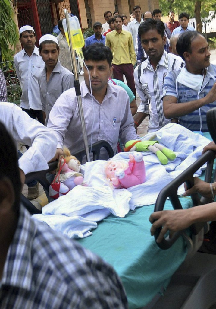 Stuffed toys lie with a 5-year-old girl being wheeled into a hospital for treatment Friday after she was raped and tortured by a man in India's capital of New Delhi.