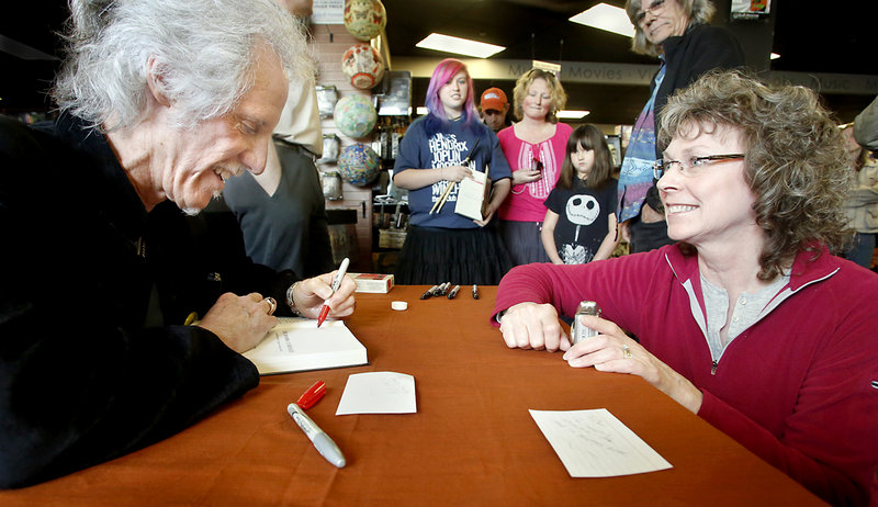 "John Densmore signs a copy of his book, ""The Doors Unhinged,"" for Leslie Bruenn of Cobalt, Conn., at Bull Moose. She and her husband, Carl Bruenn, were the first ones in line, at 9 a.m. for the 2 p.m. event."