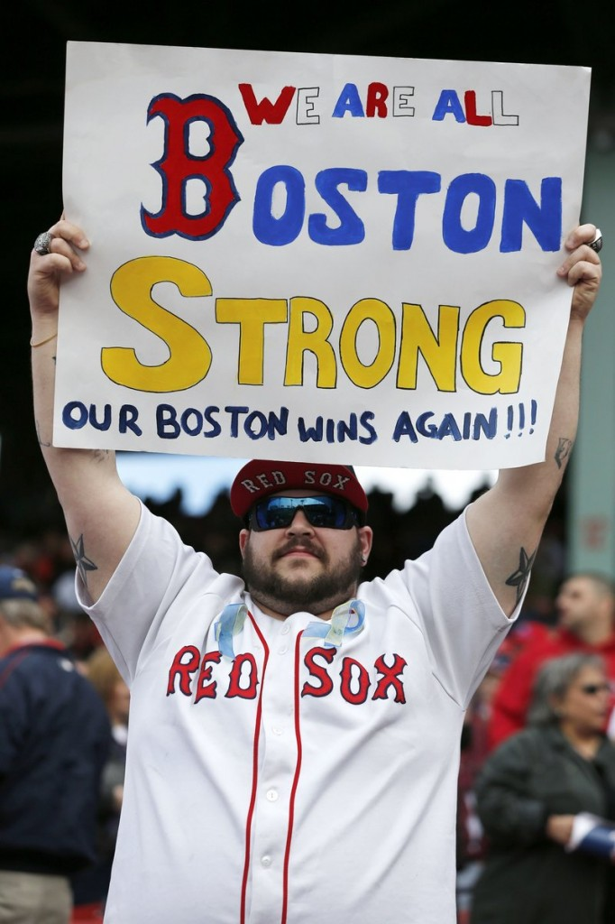 A fan holds a sign expressing the city's mood after the Boston Red Sox defeated the Kansas City Royals at Fenway Park on Saturday. Victims and survivors of the Boston Marathon bombings were honored in an emotional pregame ceremony.