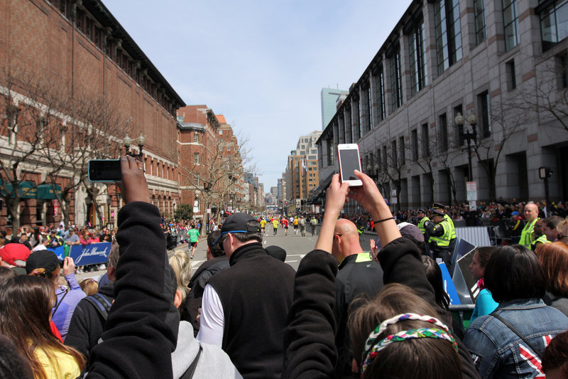 Spectators take photos with camera phones during the Boston Marathon on Monday, before two bombs exploded at the finish line in an attack that killed three people and wounded more than 180.
