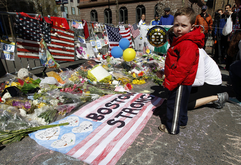 Two-year-old Wesley Brillant of Natick, Mass., stands Sunday in front of a memorial to the victims of the Boston Marathon bombings on Boylston Street. Officials plan to hold a moment of silence Monday at 2:50 p.m., the time the first bomb went off.