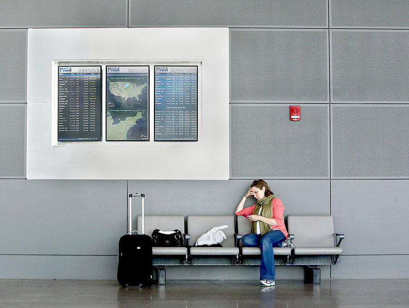 Lauren Messner of New York City waits for her delayed flight home at the Portland International Jetport on Monday afternoon. Messner said she was told when she checked in that her flight was delayed for one hour because of the air traffic controller cutbacks.
