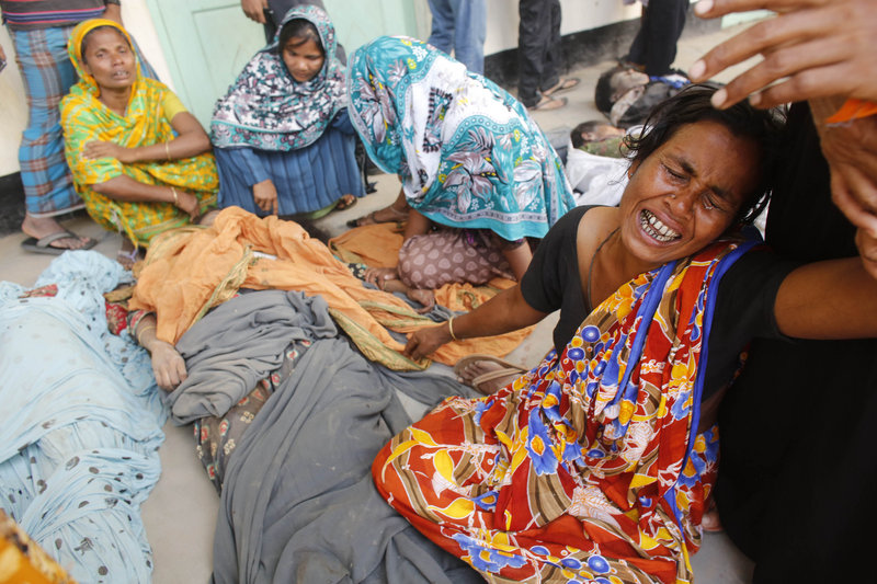 People mourn in front of the remains of their relatives who died in the collapsed Rana Plaza building in Savar, 19 miles outside Dhaka, Bangladesh, on Thursday. The number of people killed by the collapse of the building rose to 275.