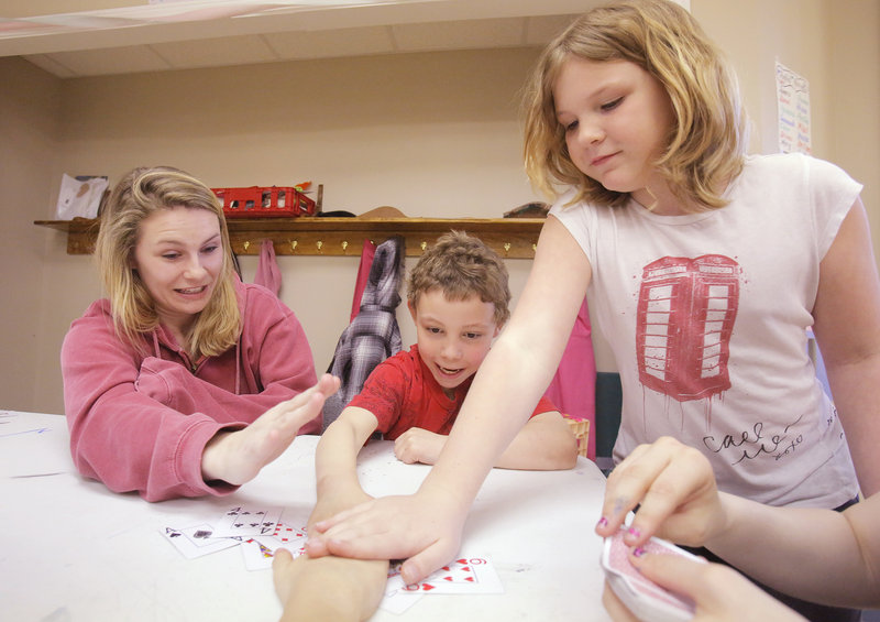 James Anderson, 8, center, and Hanna Harrington, right, play the card game Slap Jack with volunteer Kaity Shea at the Joyful Harvest Neighborhood Center in Biddeford on Thursday. The Joyful Harvest center served a total of 592 youngsters last year.