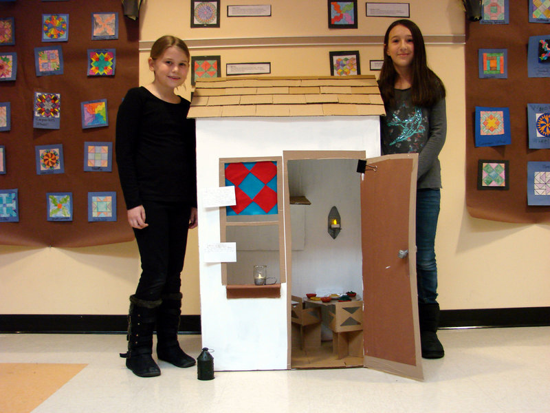 "Wells Elementary School students Amanda Ring and Isabella DeAngelis stand by a miniature cardboard replica of a safe house they created as part of a display for a class study on the ""Underground Railroad"" recently."