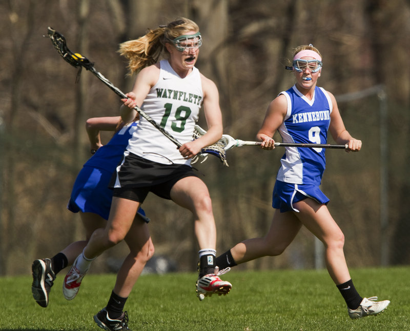 Martha Veroneau of Waynflete quickly moves the ball down the field Saturday as Samantha Bell, right, of Kennebunk pursues. Veroneau had five goals and four assists as the Flyers reached 3-0 with a 16-1 victory at home.