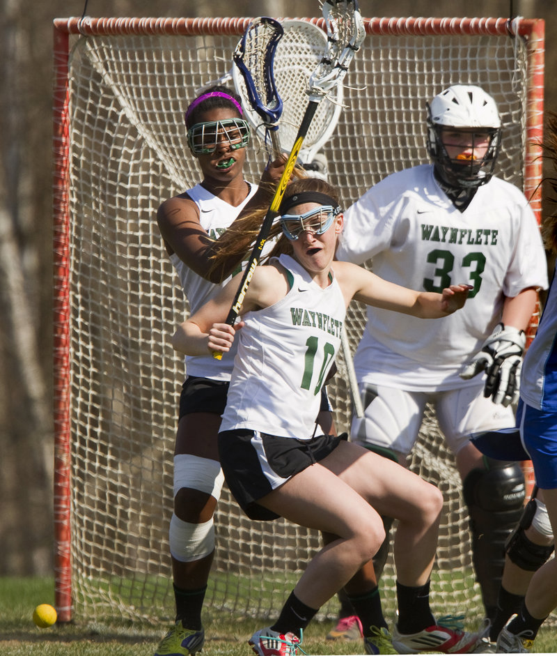 Amelia Deady of Waynflete keeps her focus on a loose ball while continuing to help defend the net in front of goaltender Katherine Torrey.