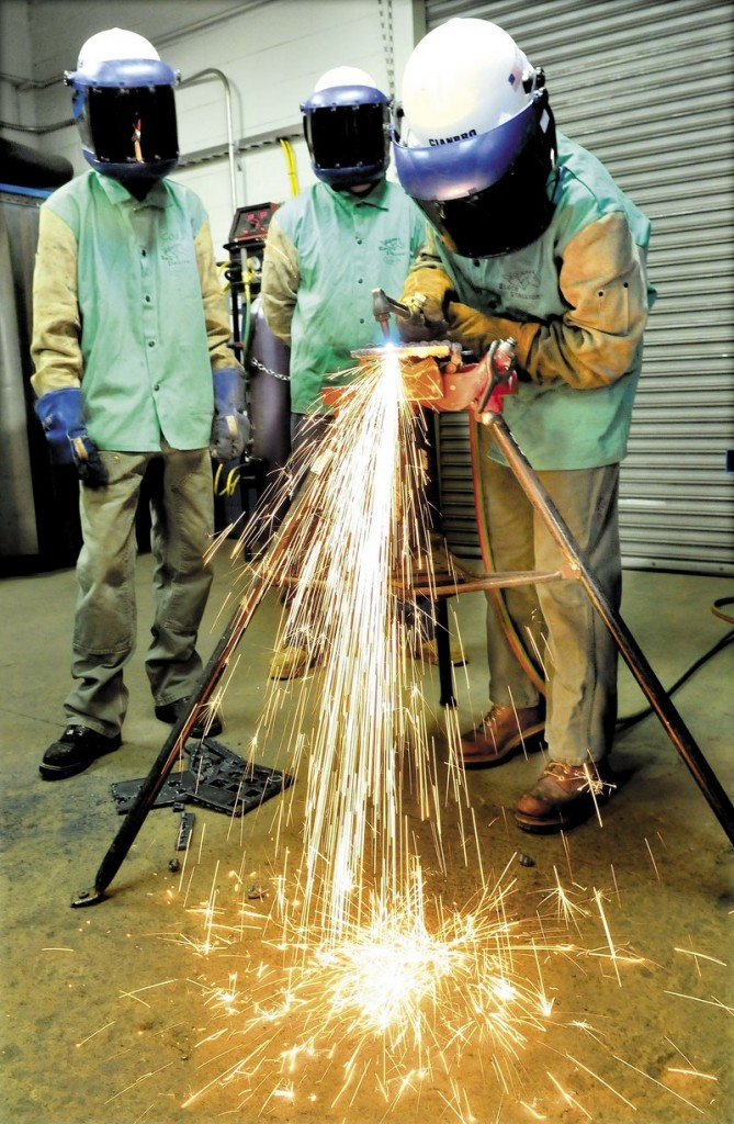 Sarah Finnemore uses a cutting torch to cut steel at the Cianbro company welding training center in Pittsfield.