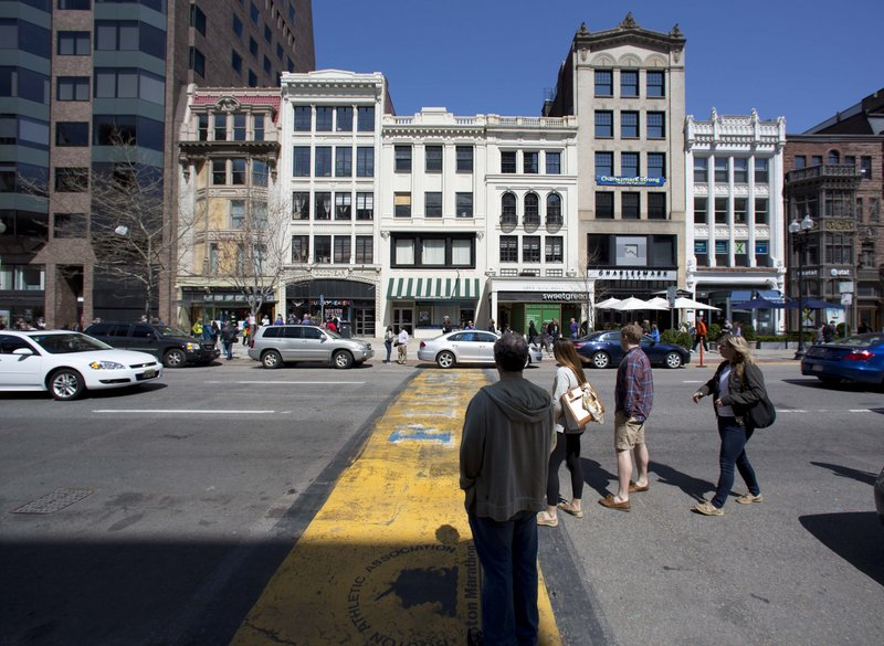 People pause on Boylston Street at the finish line of the Boston Marathon last Saturday. A pedestrian who strolls through Boston's Financial District can be seen by at least 233 private and public cameras.