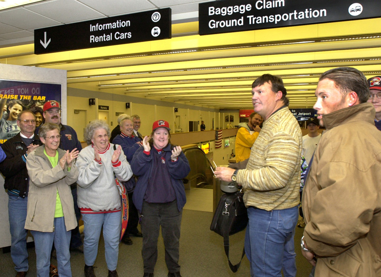 Staff Photo by John Patriquin, Tue, Apr 01, 2003: Portland Sea Dogs loyal fans Carol Spencer, Shirley Bibber, and Susie Konkel greet Sea Dogs manager Ron Johnson and pitcher James Johnson as the team arrived at the Portland Jetport tonight.