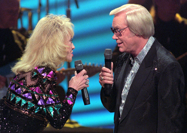 Tammy Wynette, left, and George Jones, right, perform during the Country Music Association Awards show in 1995.