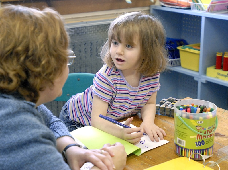 In this December 2007 file photo, teacher Anne Sprague works with 4-year-old Trinity Ramsay and other preschoolers in a reading class at St. Elizabeth's Children Center in Portland. Business leaders and children's advocates gathered at the State House on Wednesday to urge state officials to make a greater investment in early childhood education programs, citing a new report that details the benefits.