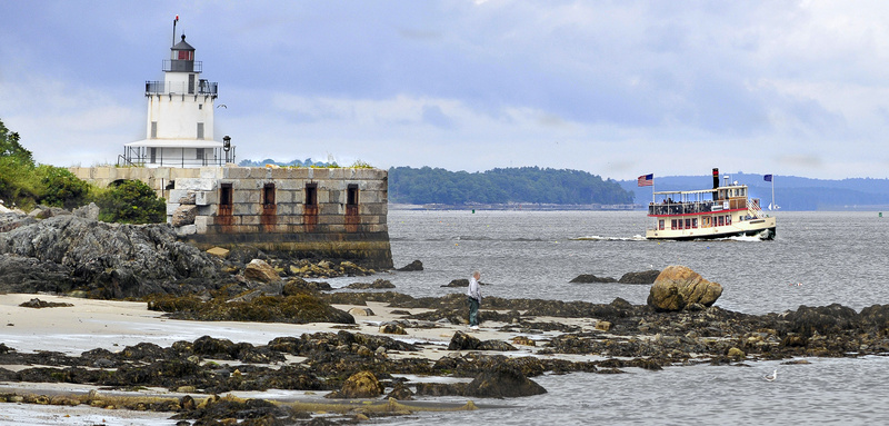 A tourist boat passes Spring Point Ledge Lighthouse as a solitary visitor enjoys Willard Beach near Fort Preble in South Portland.