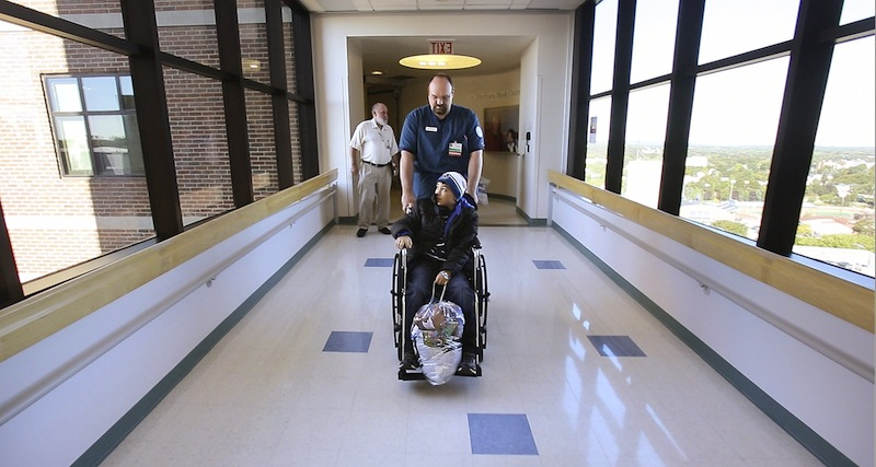 In this September 2012 file photo, a patient is wheeled out of Barbara Bush Children's Hospital at Maine Medical Center in Portland. Maine Democrats in the Legislature continued their push Wednesday for an expansion of publicly funded health insurance for low-income Mainers and moved to link the expansion with Gov. Paul LePage's plan to pay hospitals about $484 million in outstanding Medicaid reimbursements.