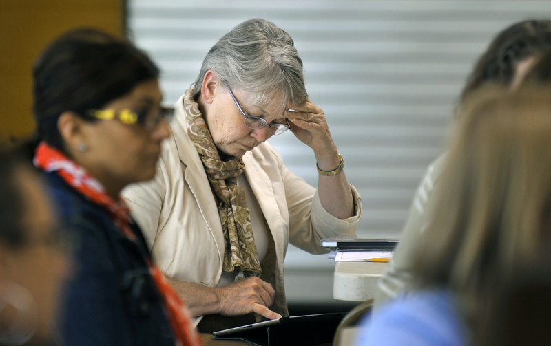 Susie Winslow, a teacher at the East End Community School, studies the report card the state gave the school during a staff meeting Wednesday. The state gave the school an F.