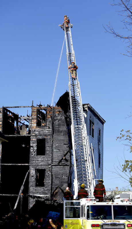 Firefighters spray water on what's left of the roof of a vacant apartment building on Bartlett Street in Lewiston on Monday.