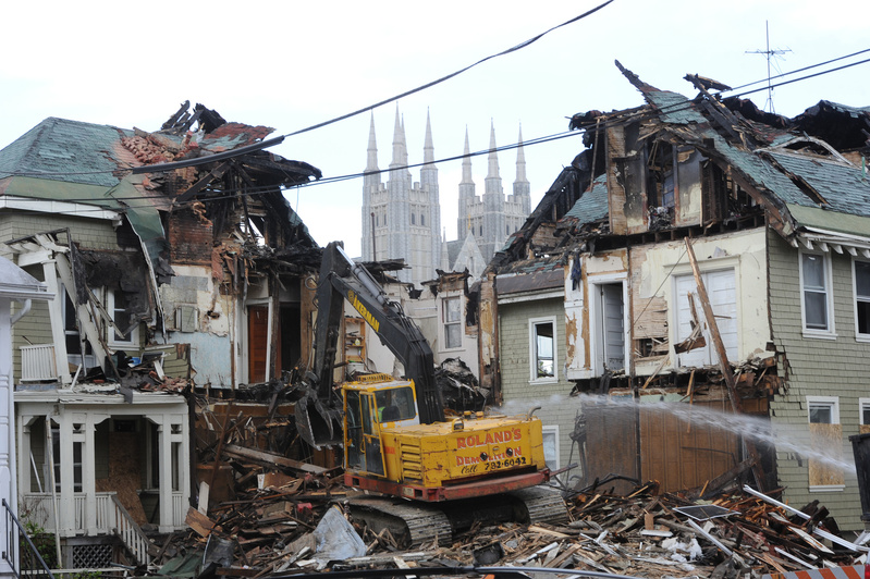 A demolition crew tears down 80-82 Pine St. in Lewiston on Friday while Maine Sen. Angus King tours the site with city officials. In the background are the spires of the Basilica of Saints Peter and Paul. King