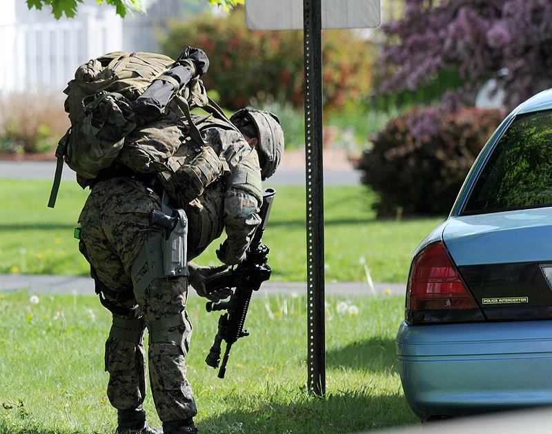 John Patriquin/Staff Photographer A member of the Maine State Police tactical unit loads his weapon as he joins dozens of state and local police officers on Hillview Avenue in Saco during Saturday's standoff with a man identified as Charles Scontras.